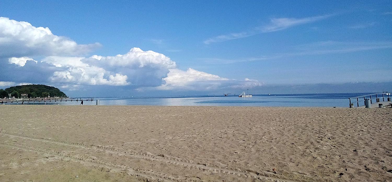 Travemünde an der Ostsee: Strand und Meer, sehr blauer Himmel, von links dicke weiße Wolkenberge.