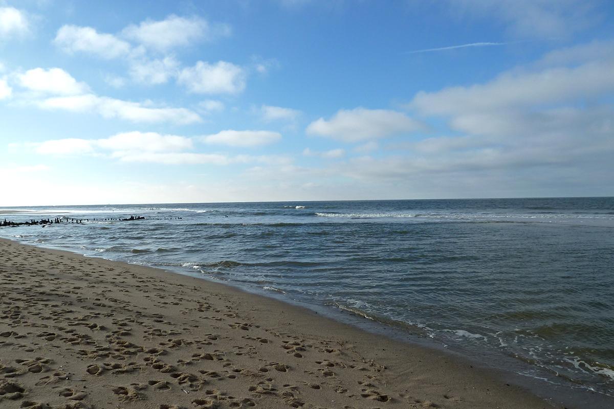 Strand bei Westerland / Sylt. Viele Spuren von Menschen im Sand, die Menschen selbst sind nicht im Bild. Die Nordsee ist relativ ruhig, es gibt nur kleine Wellen. Am blauen Himmel weiche mittelkleine Wolken.